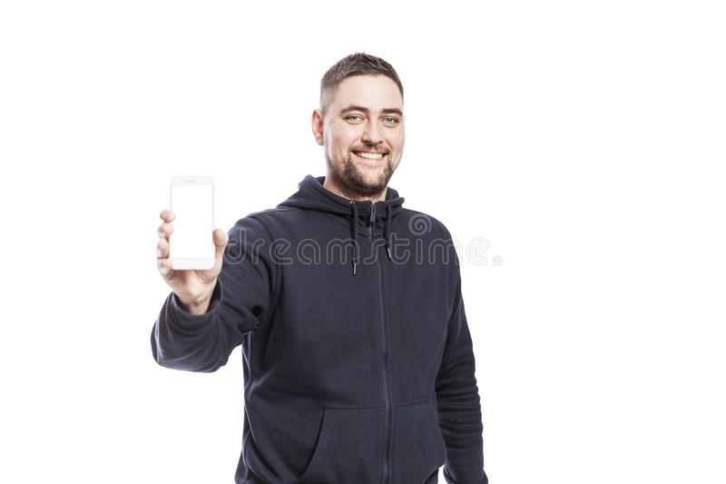 Cute smiling young man shows a phone with an isolated screen. Isolated over white background stock photos