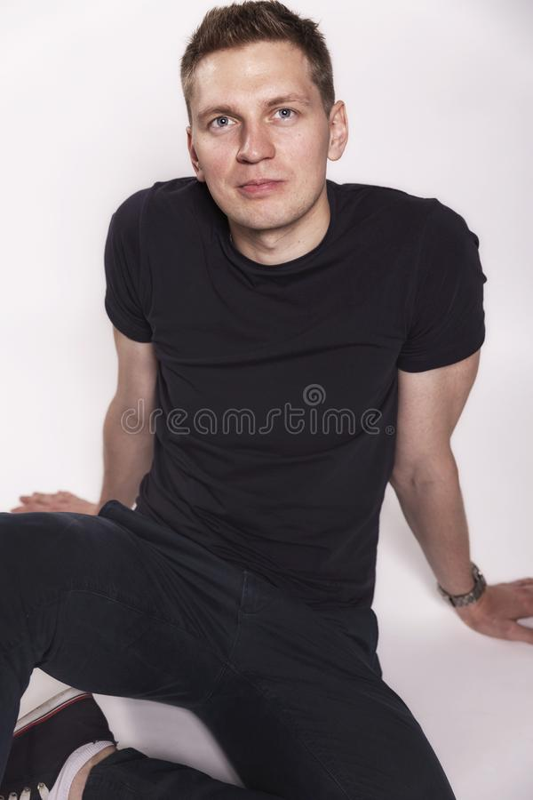 Cute smiling young man sitting on the floor royalty free stock images