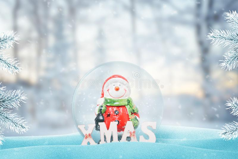 Cute snowman in Santa Claus clothes in New Year, Christmas glass magic ball. Snow fall on it and Christmas tree beside stock photo