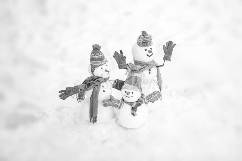 Cute snowmen family in winter Christmas landscape. Happy winter snowman family. Mother snow-woman, father snow-man and. Kid wishes merry Christmas and Happy New stock image