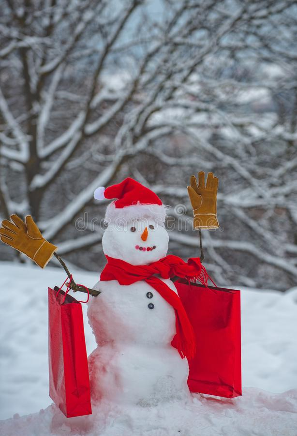 Cute snowmen with - gift presents standing in winter Christmas landscape. Happy snowman with Christmas gift standing in. Winter Christmas landscape stock photography