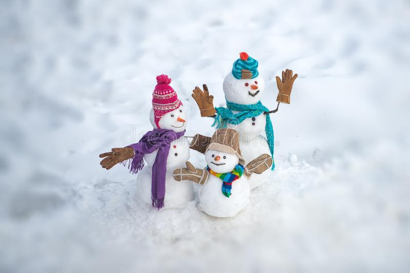 Cute snowmen standing in winter Christmas landscape. Happy winter snowman family. Mother snow-woman, father snow-man and. Kid wishes merry Christmas and Happy stock photo
