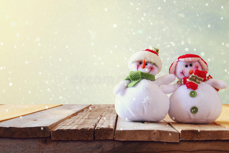 Cute snowmen on wooden table royalty free stock photos