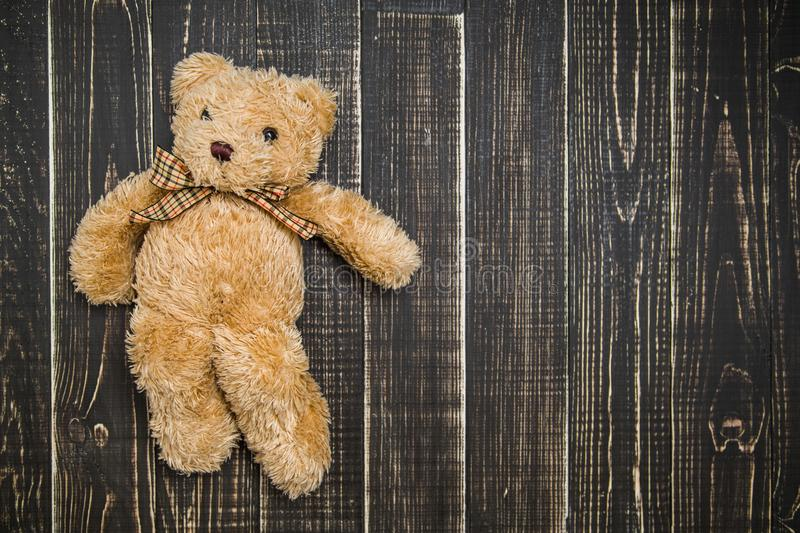 Cute soft brown teddy bear laying on wooden shabby background stock photos