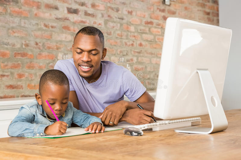 Cute son doing his homework with father. In living room stock photos