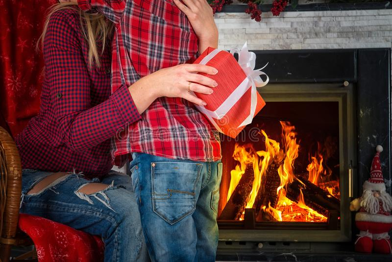 Merry Christmas and Happy Holidays!Cute son gives his beloved mother a gift.New year`s interior in the living room with fireplace stock images