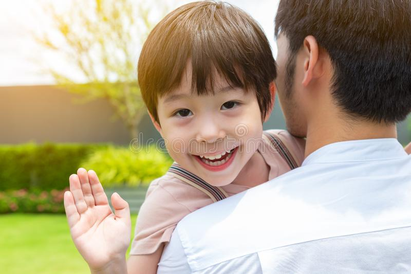 Cute son or little boy so happy when meet his father with smiley face. Lovely child does not meet his father for long time, Dad. Work at foreign country. Dad stock image