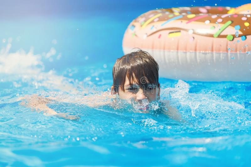 Cute sporty boy swims in the pool with donut ring and has fun, smiles, holds oranges. vacation with kids, holidays, active weekend. S concept royalty free stock images