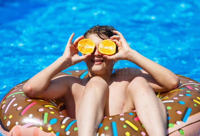 Cute sporty boy swims in the pool with donut ring and has fun, smiles, holds oranges. vacation with kids, holidays, active weekend. S concept stock image