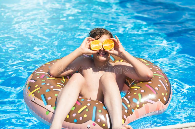 Cute sporty boy swims in the pool with donut ring and has fun, smiles, holds oranges. vacation with kids, holidays, active weekend. S concept stock photography