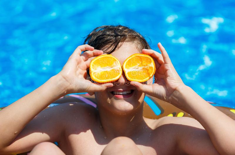 Cute sporty boy swims in the pool with donut ring and has fun, smiles, holds oranges. vacation with kids, holidays stock photography
