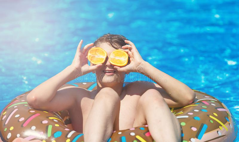 Cute sporty boy swims in the pool with donut ring and has fun, smiles, holds oranges. vacation with kids, holidays, stock photos