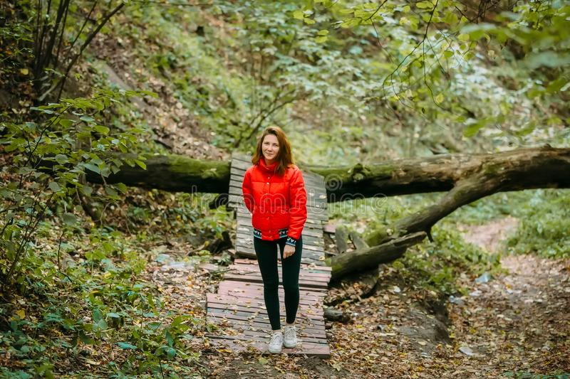 Cute sporty girl in red jacket is walking in forest. Autumn. Artwork royalty free stock photos
