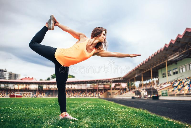 Cute sporty girl showing stretching exercises outdoor royalty free stock photo