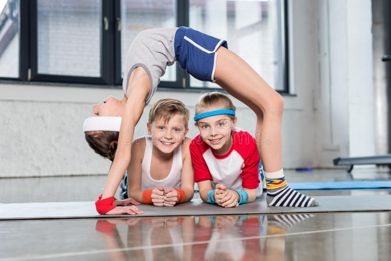 Cute sporty kids exercising in gym and smiling at camera. Children sport school concept stock images