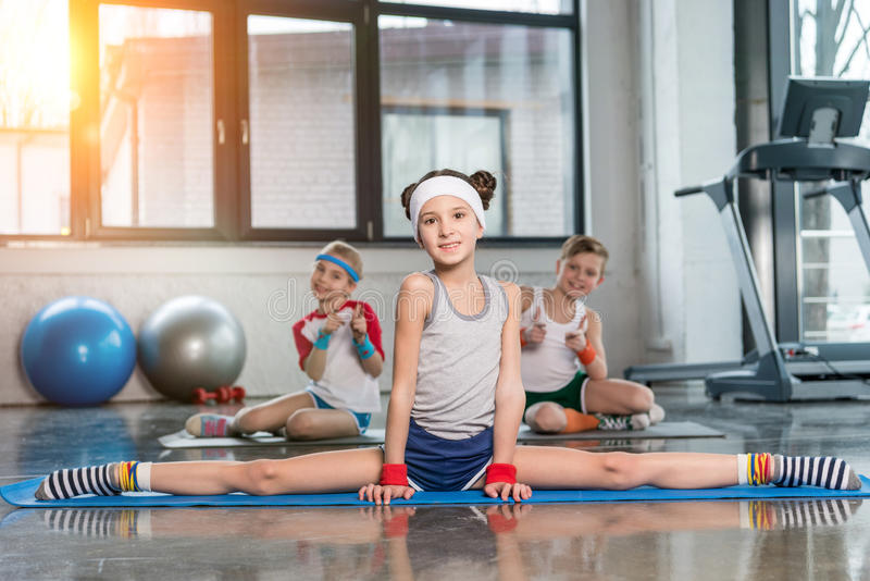 Cute sporty kids exercising in gym and smiling at camera. Children sport school concept stock image