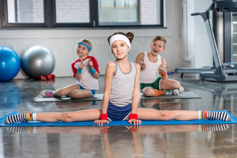 Cute sporty kids exercising in gym and smiling at camera. Children sport school concept stock photography