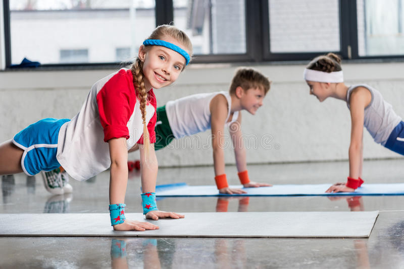 Cute sporty kids exercising on yoga mats in gym and smiling. Children sport school concept stock photography