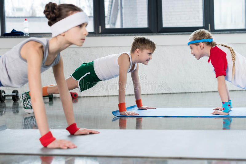Cute sporty kids exercising on yoga mats in gym and smiling. Children sport school concept royalty free stock images