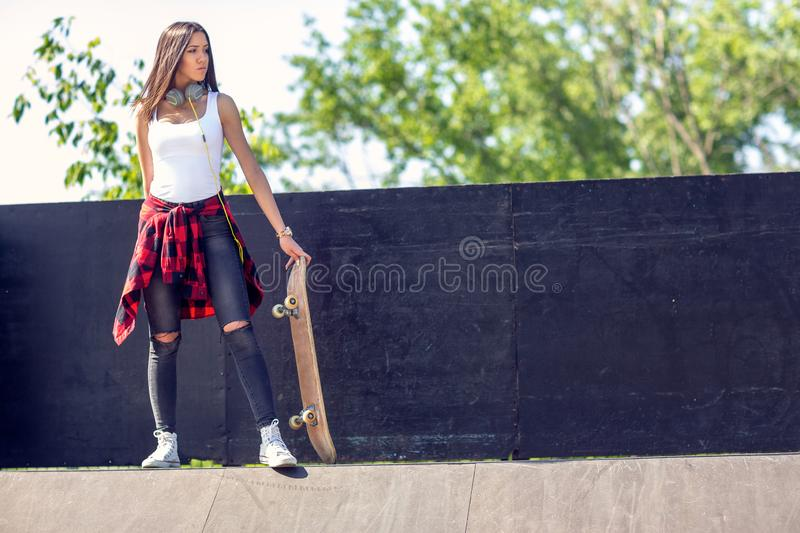 Sporty teen girl with skateboard. Outdoors, urban lifestyle. Cute sporty teen girl with skateboard. Outdoors, urban lifestyle royalty free stock photos