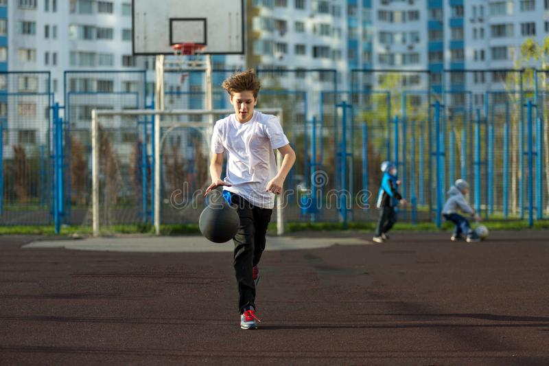 Cute sporty teenage boy playing basketball outdoors preparing for shooting. active lifestyle. Sport royalty free stock image