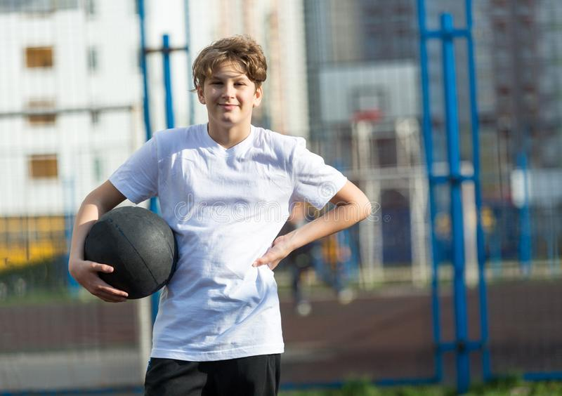 Cute sporty teenage boy in white t shirt plays basketball outdoors preparing for shooting. healthy sport lifestyle royalty free stock image