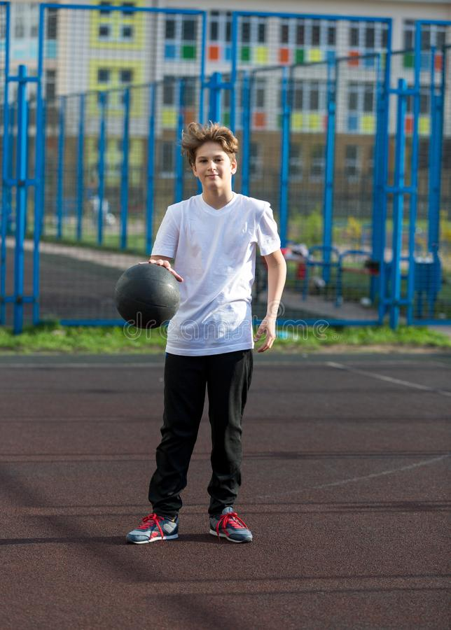 Cute sporty teenage boy in white t shirt plays basketball outdoors preparing for shooting. healthy sport lifestyle. Concept for kids stock photography