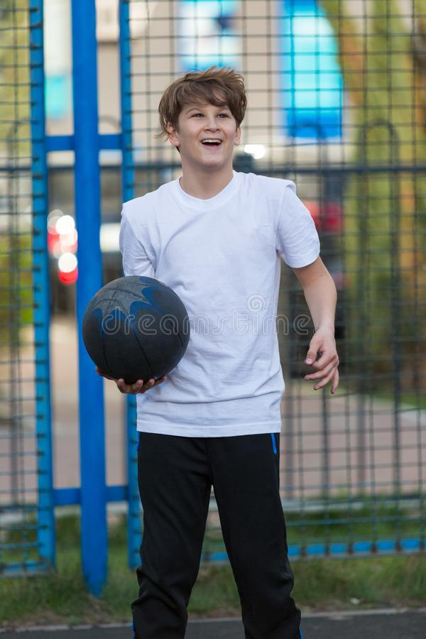 Cute sporty teenage boy in white t shirt plays basketball outdoors preparing for shooting. healthy sport lifestyle. Concept for kids royalty free stock photo
