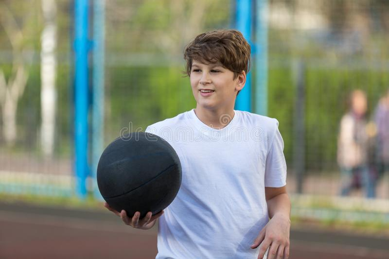 Cute sporty teenage boy in white t shirt plays basketball outdoors preparing for shooting. healthy sport lifestyle. Concept for kids royalty free stock image