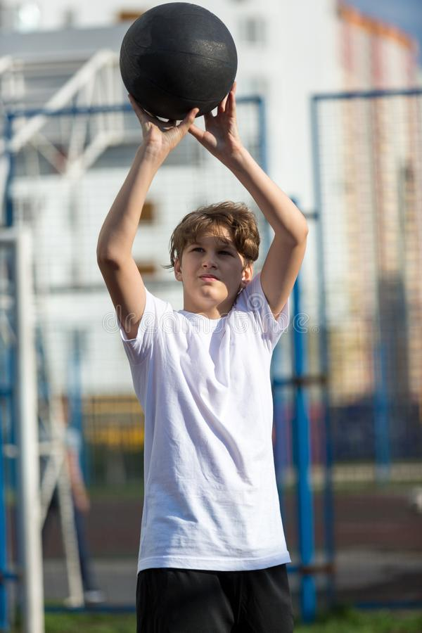 Cute sporty teenage boy in white t shirt plays basketball outdoors preparing for shooting. healthy sport lifestyle. Concept for kids royalty free stock photos
