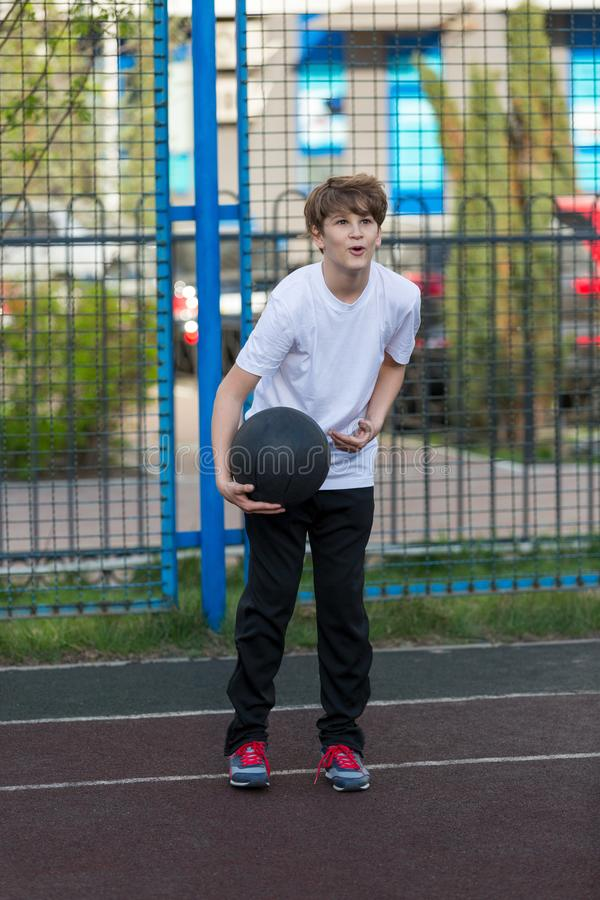 Cute sporty teenage boy in white t shirt plays basketball outdoors preparing for shooting. healthy sport lifestyle. Concept for kids stock photos