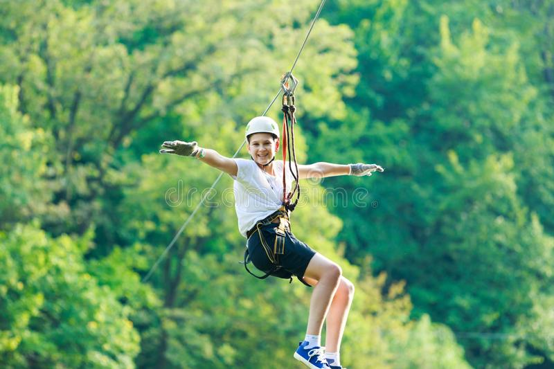 Cute, sporty young boy in helmet and white t shirt in the rope adventure park in the summer. Active sport life stock photo