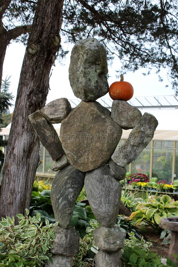 Cute stone sculpture with small pumpkin balanced on shoulder, seen at popular nursery Connecticut, 2018 stock image