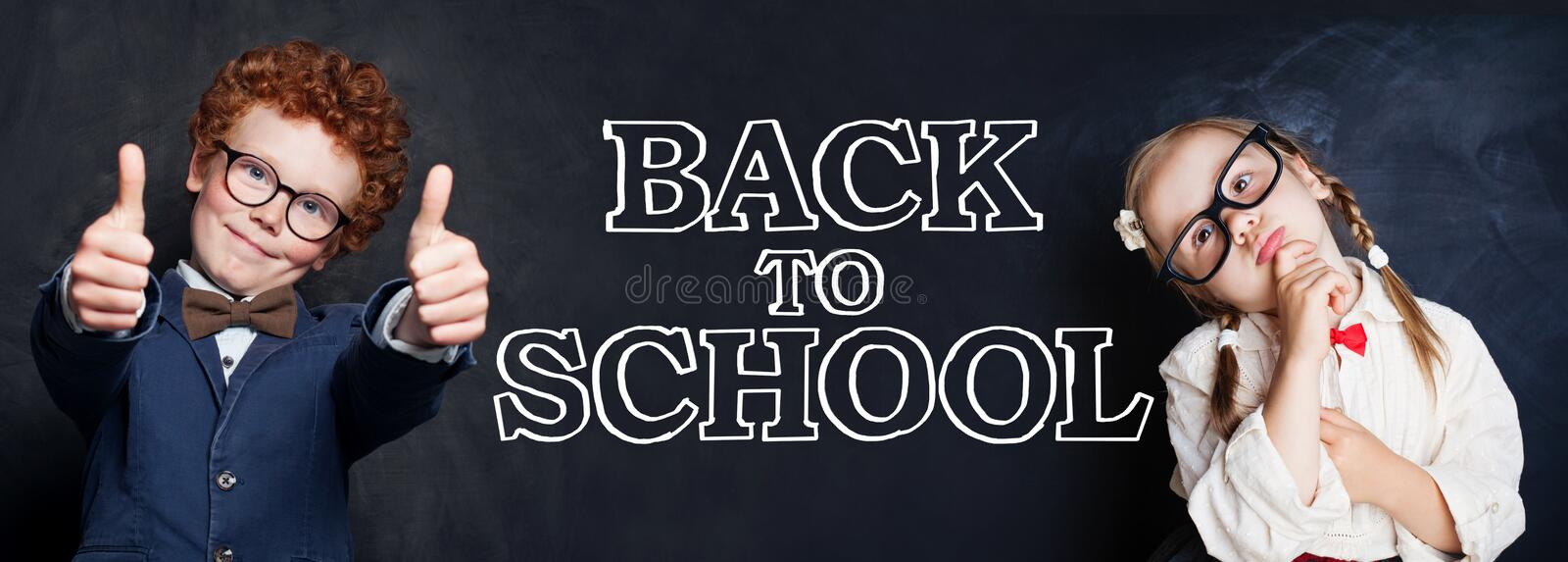 Cute student kids little boy and girl thinking, showing thumb up and having fun against chalkboard background. Back to school stock photo