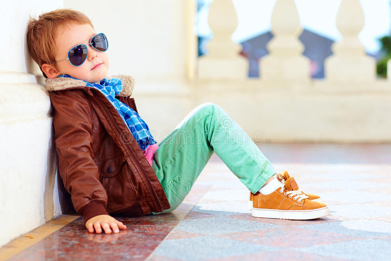 Cute stylish boy in leather jacket and gum shoes royalty free stock photography