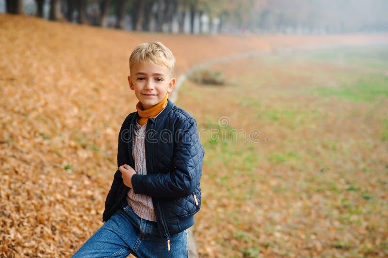 Cute stylish boy on a walk in autumn. Schoolboy outdoors portrait. Autumn fashion. Happy autumn holidays. Handsome blonde boy royalty free stock image