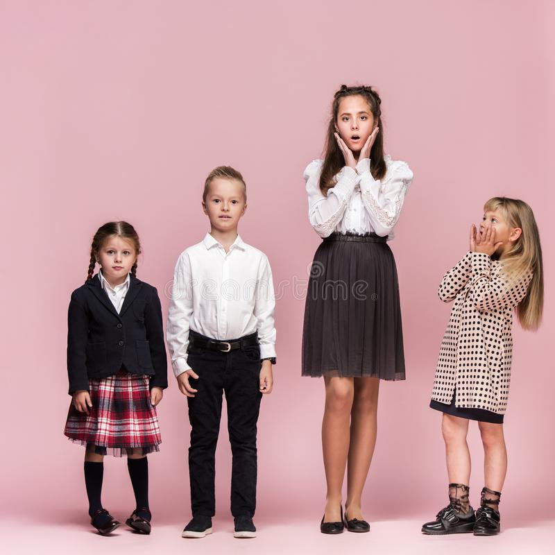Cute stylish children on pink studio background. The beautiful teen girls and boy standing together. Cute surprised stylish children on pink background stock images