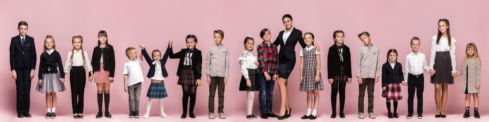 Cute stylish children on pink studio background. The beautiful teen girls and boy standing together. Cute smiling happy stylish children and female teacher on stock photos