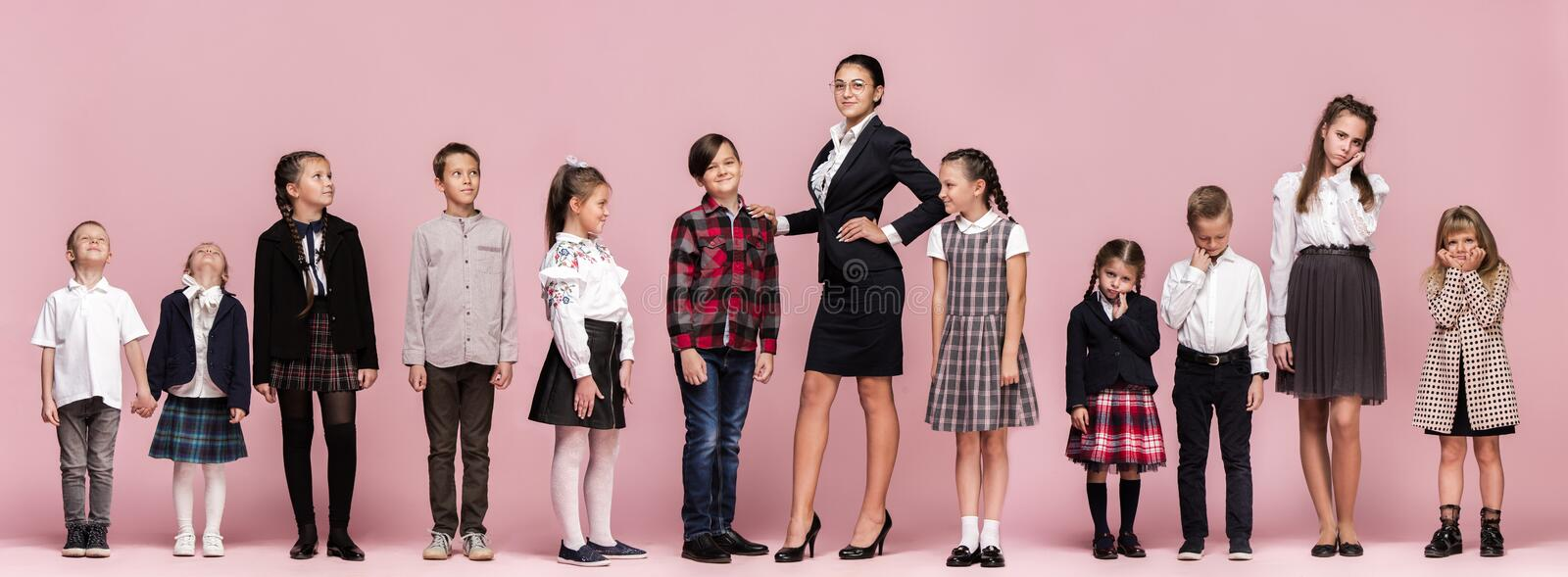 Cute stylish children on pink studio background. The beautiful teen girls and boy standing together stock photography