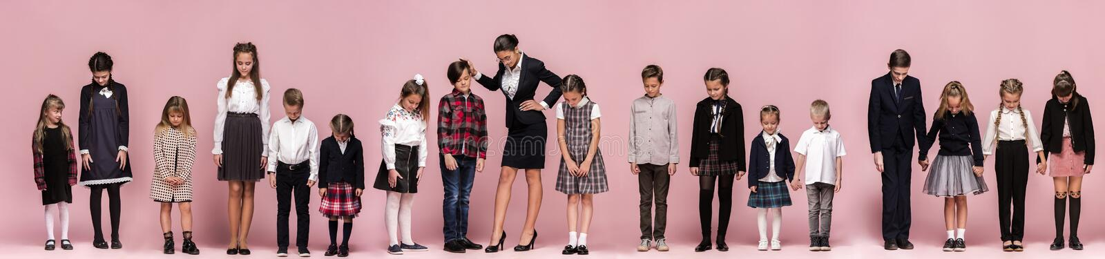 Cute stylish children on pink studio background. The beautiful teen girls and boy standing together stock photos