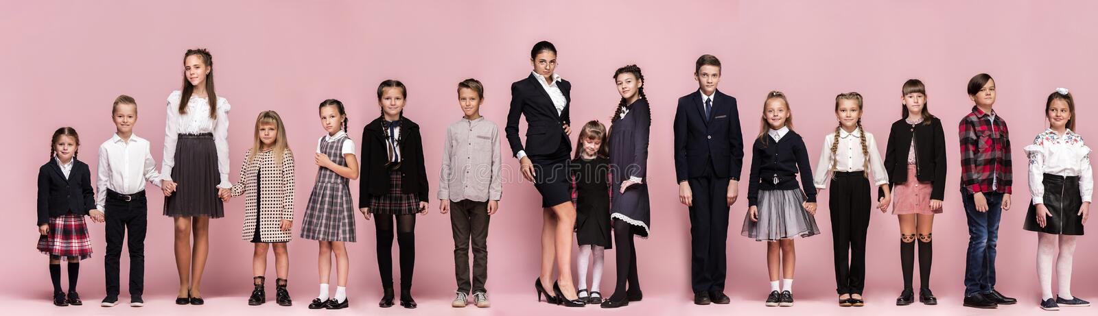 Cute stylish children on pink studio background. The beautiful teen girls and boy standing together royalty free stock image