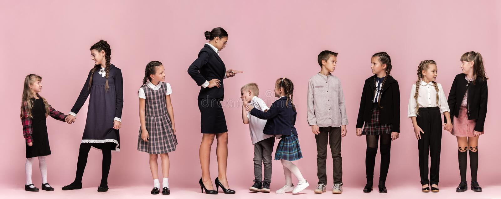 Cute stylish children on pink studio background. The beautiful teen girls and boy standing together royalty free stock photo