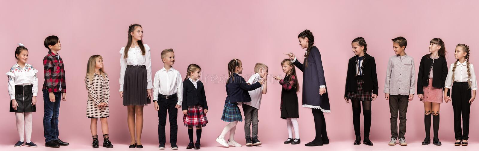 Cute stylish children on pink studio background. The beautiful teen girls and boy standing together stock images