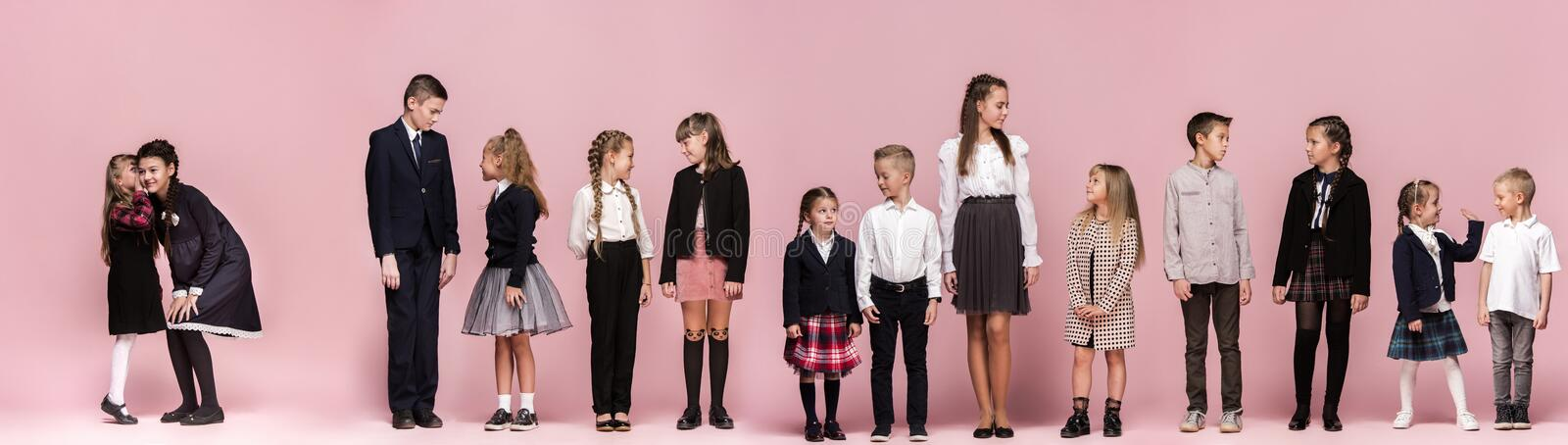 Cute stylish children on pink studio background. The beautiful teen girls and boy standing together stock image