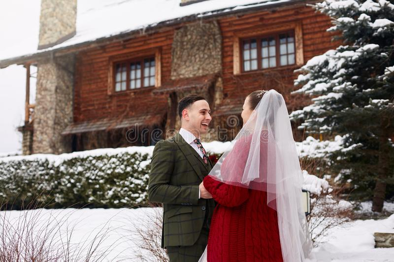 Cute stylish couple on wedding day. Bride and groom meet for the first time. First look. Winter wedding on snowfall with stock photography