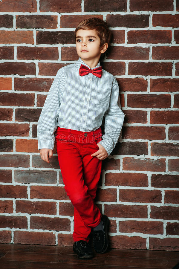 Cute stylish little boy staying near the brick wall in red pants and red bow tie. Kids, boy stock photos