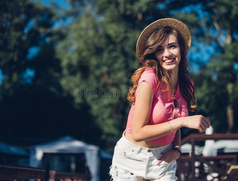 Cute summer fashion portrait of beauty brunette woman having fun on the beach, dancing and smiling, vacation mood.Nice laughing gi stock photo