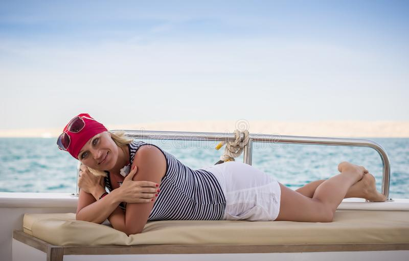 Cute sunburnt girl in white shorts is lying on a leather couch on a motor yacht on background of the turquoise sea stock photography