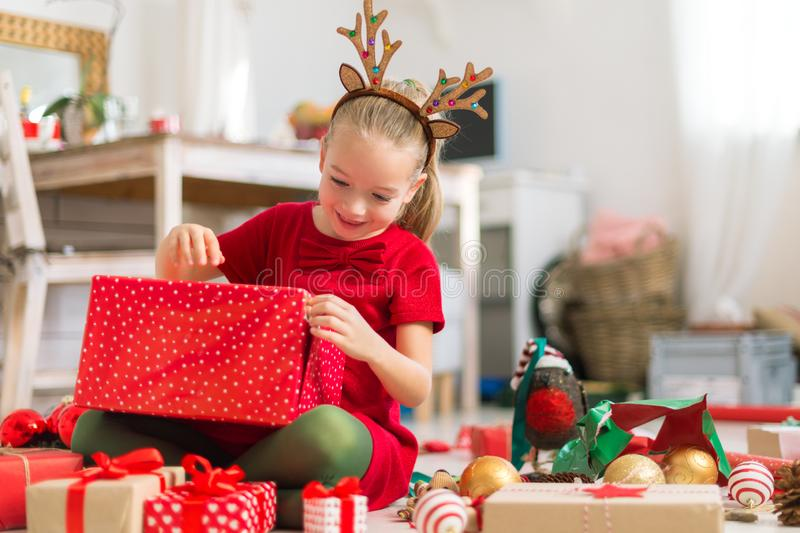 Cute super excited young girl opening large red christmas present while sitting on living room floor. Candid family christmas time. Cute super excited young girl royalty free stock photos