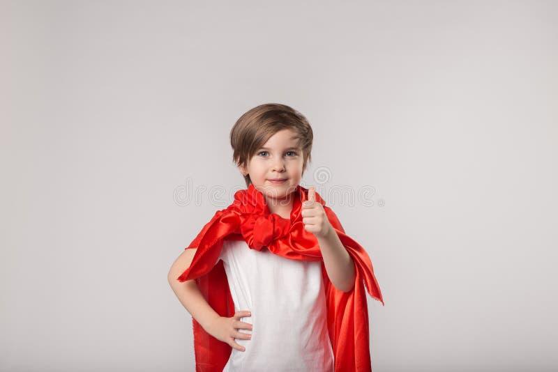 Cute superhero kid give thumbs up. Little girl in superhero costume stock images